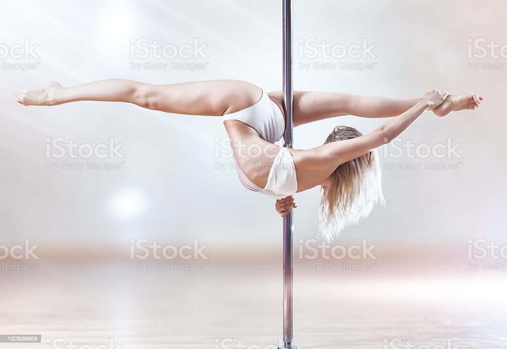 Young woman on white bikini dancing on a pole stock photo