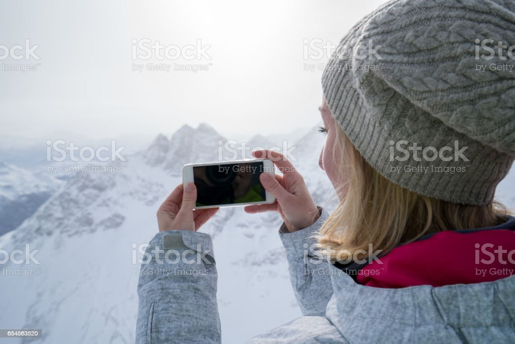 Young woman onthe ski slopes taking a smart phonw picture stock photo