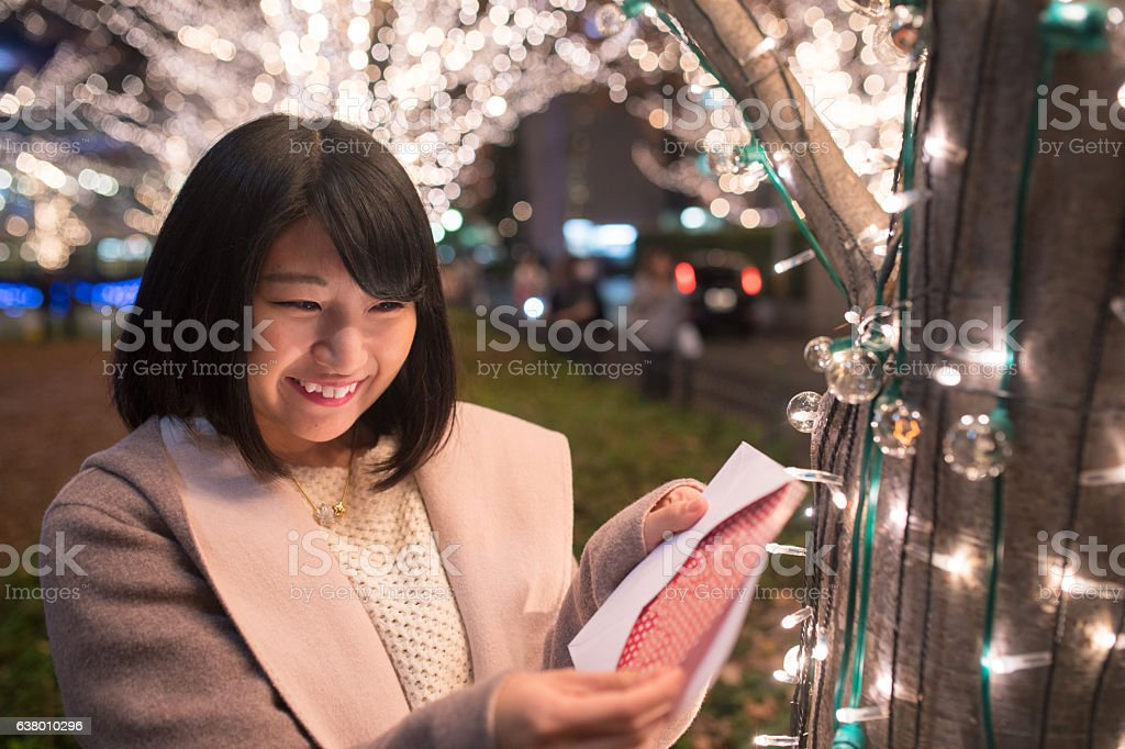 Young woman opening Christmas card under Christmas lights stock photo