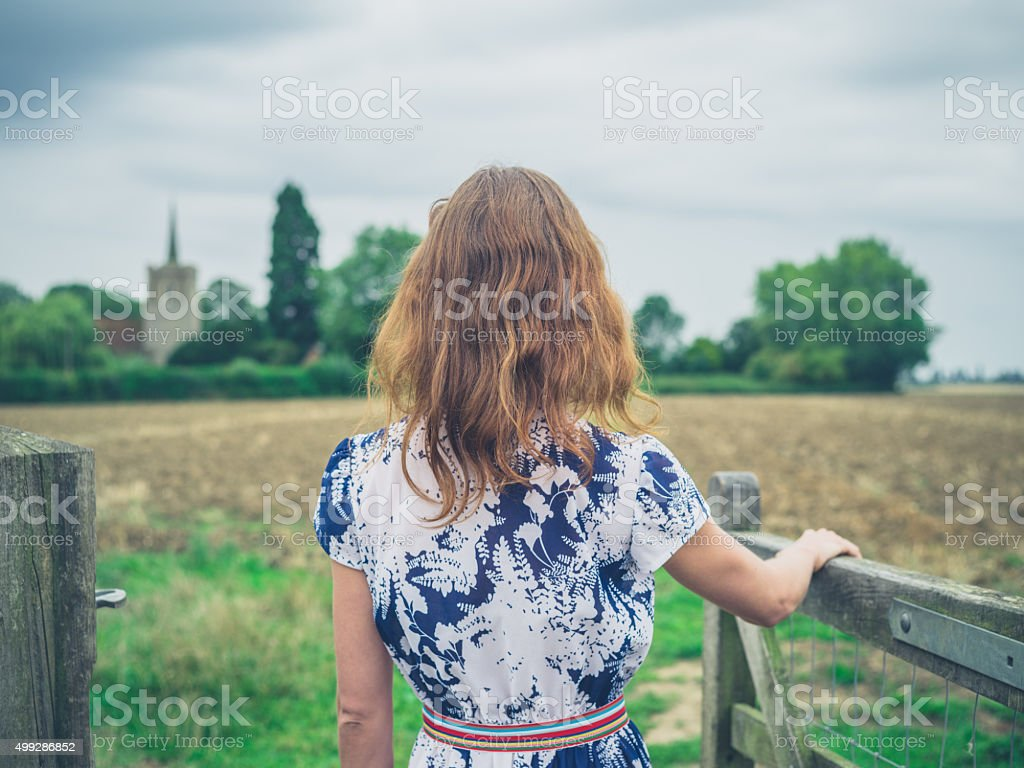 Young woman opening gate in the country stock photo