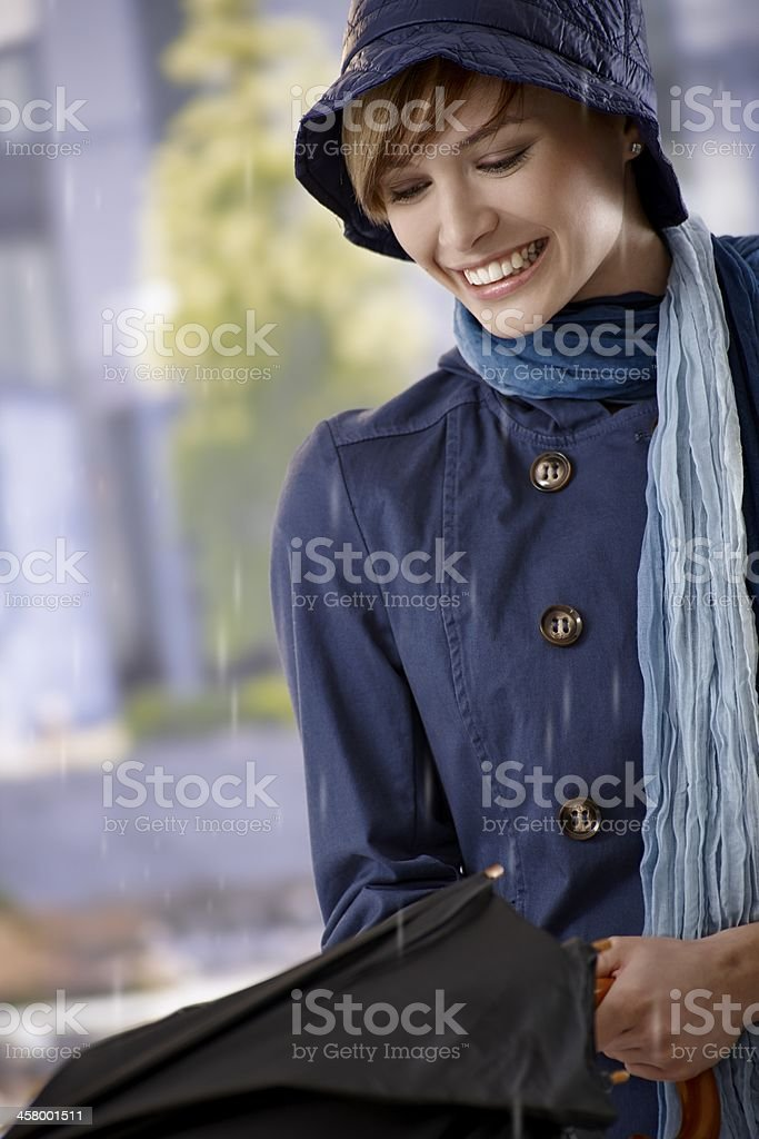 Young woman opening umbrella in rain stock photo