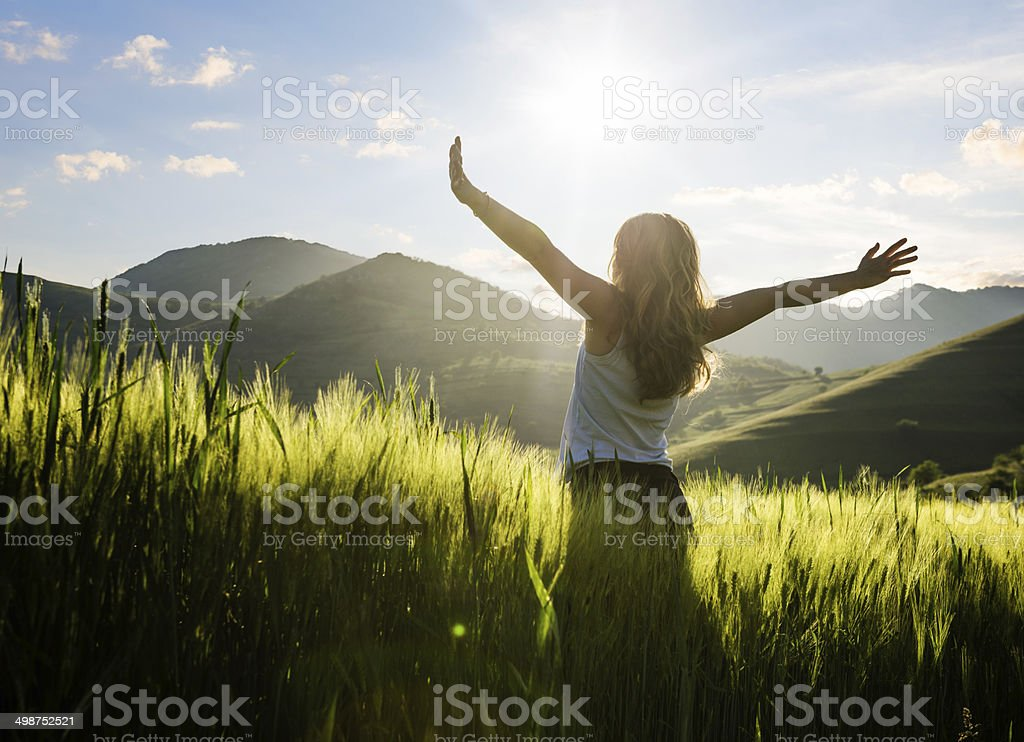 Young woman outdoor in the field enjoying the sun stock photo
