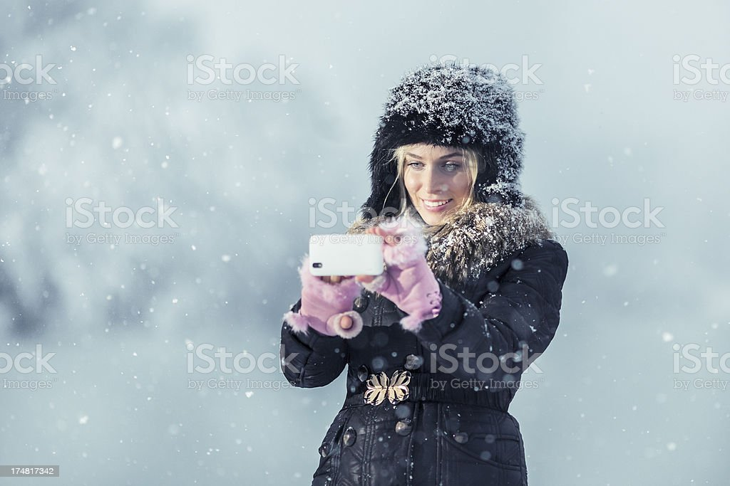 Young woman outdoor photographing snow on a winter day royalty-free stock photo