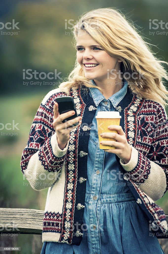 Young woman outdoor with her smartphone - V royalty-free stock photo