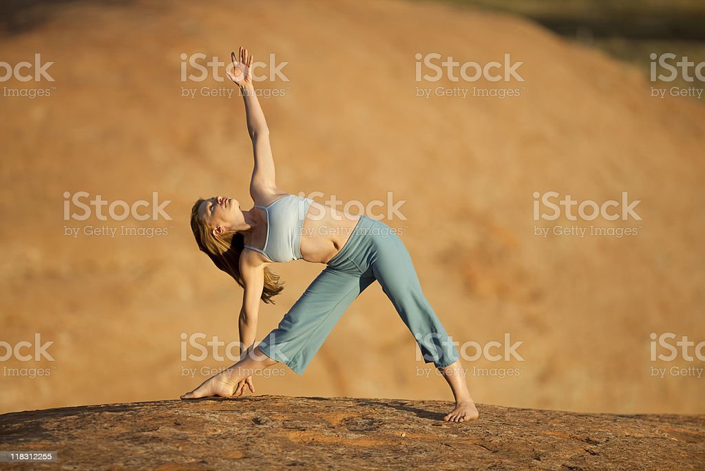 Young Woman Outdoors Practicing Yoga In Triangle Pose royalty-free stock photo