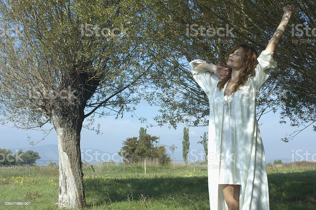 Young woman outdoors, stretching, eyes closed stock photo