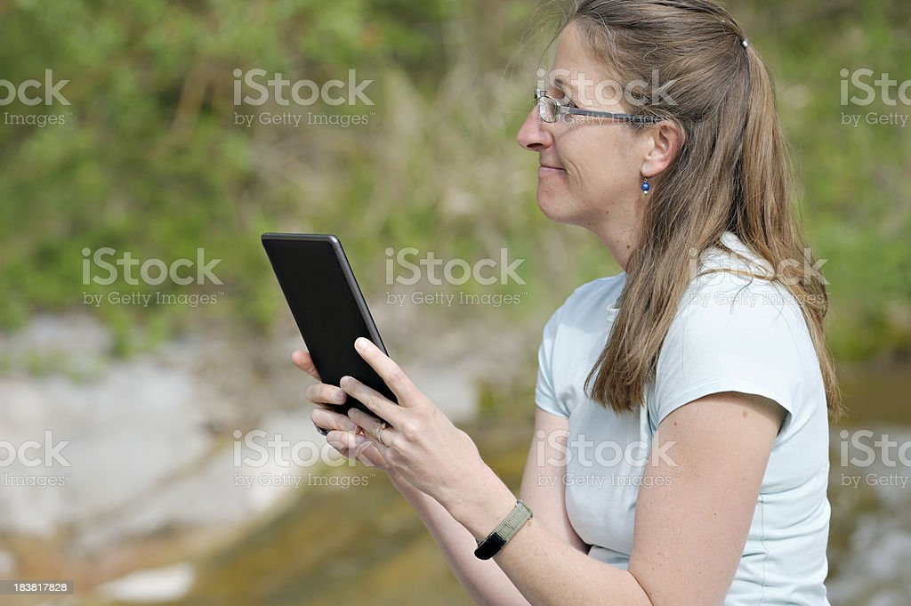 Young woman outdoors with e-reader stock photo