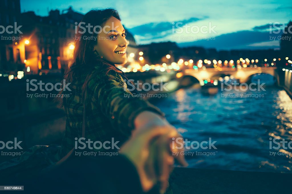 Young woman outstretching hands on river bridge by night stock photo