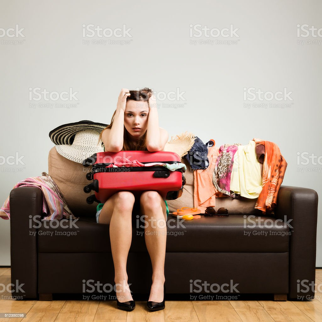 Young woman packing a travel bag on the plane. stock photo