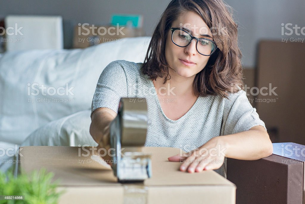 Young woman packing for a house move a cardboard box stock photo