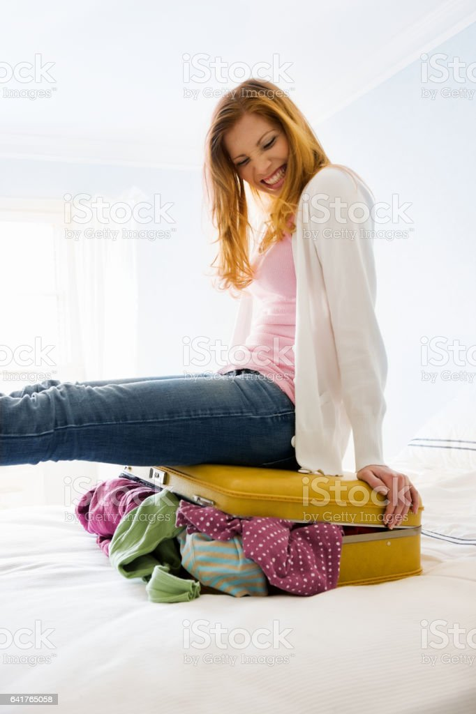 Young Woman Packing Luggage stock photo
