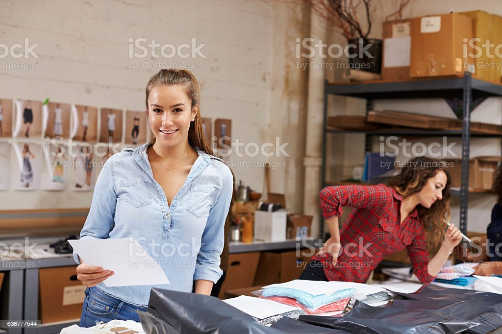 Young woman packing orders for distribution smiles to camera stock photo