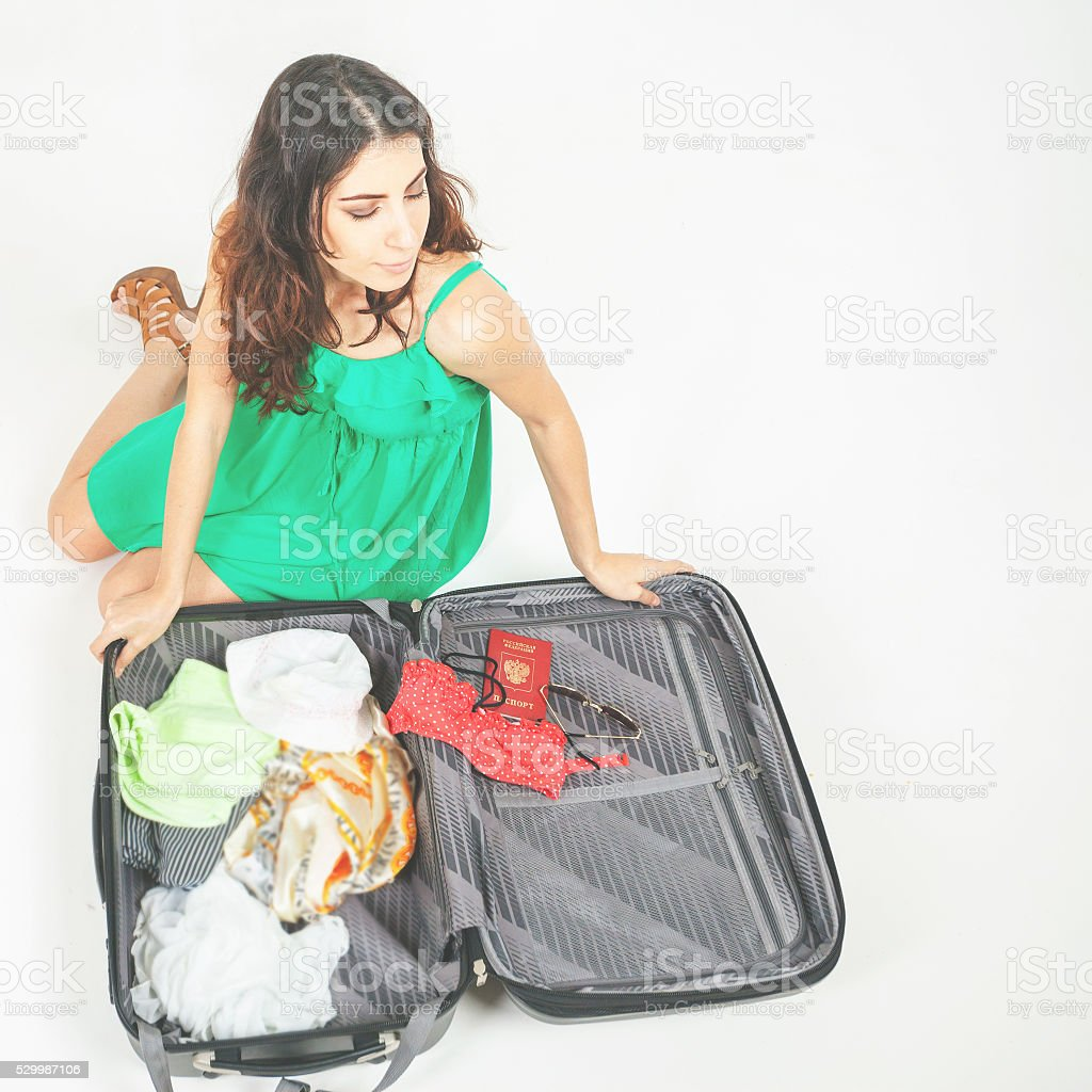 Young woman packs her things, clothes at full luggage stock photo