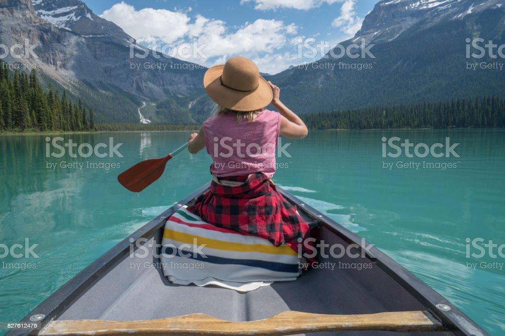 Junge Frau rote Kanu auf türkisfarbenen See paddeln – Foto