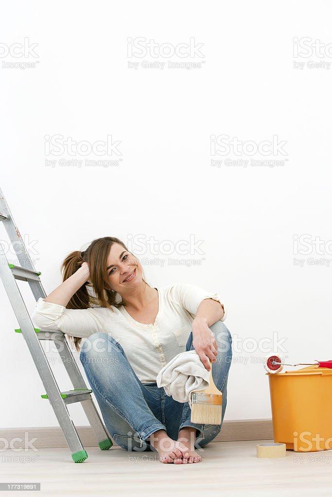 Peintre Jeune femme assise sur le sol après des travaux de peinture. photo libre de droits
