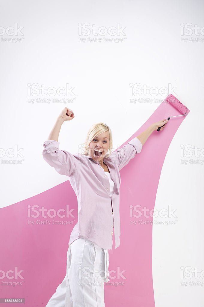 Young Woman Painting a Wall Pink royalty-free stock photo