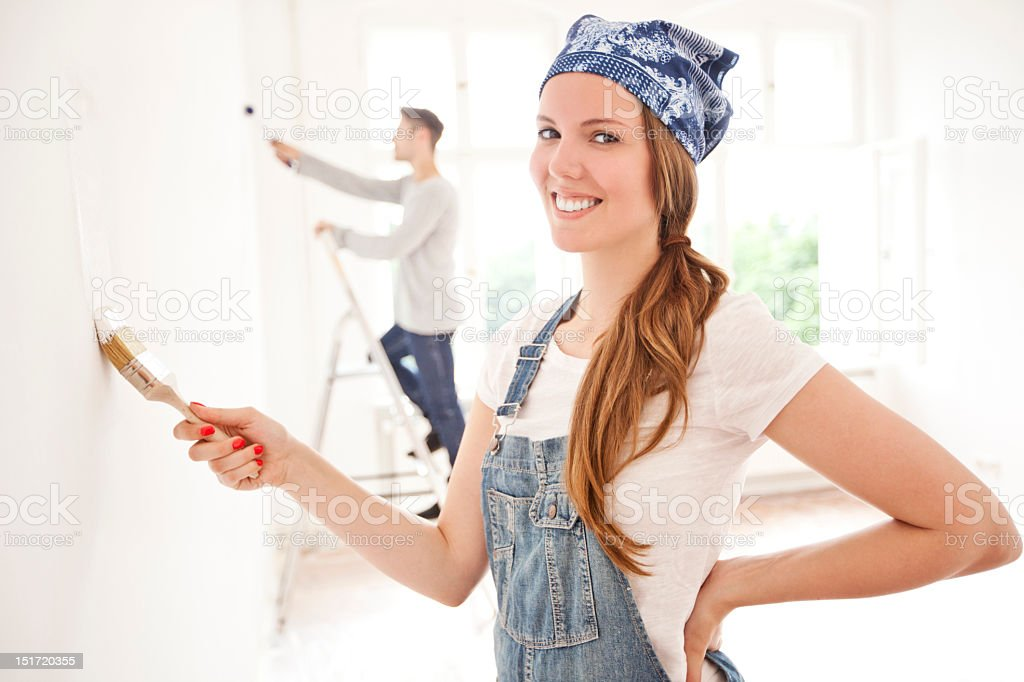 Young woman painting her house stock photo