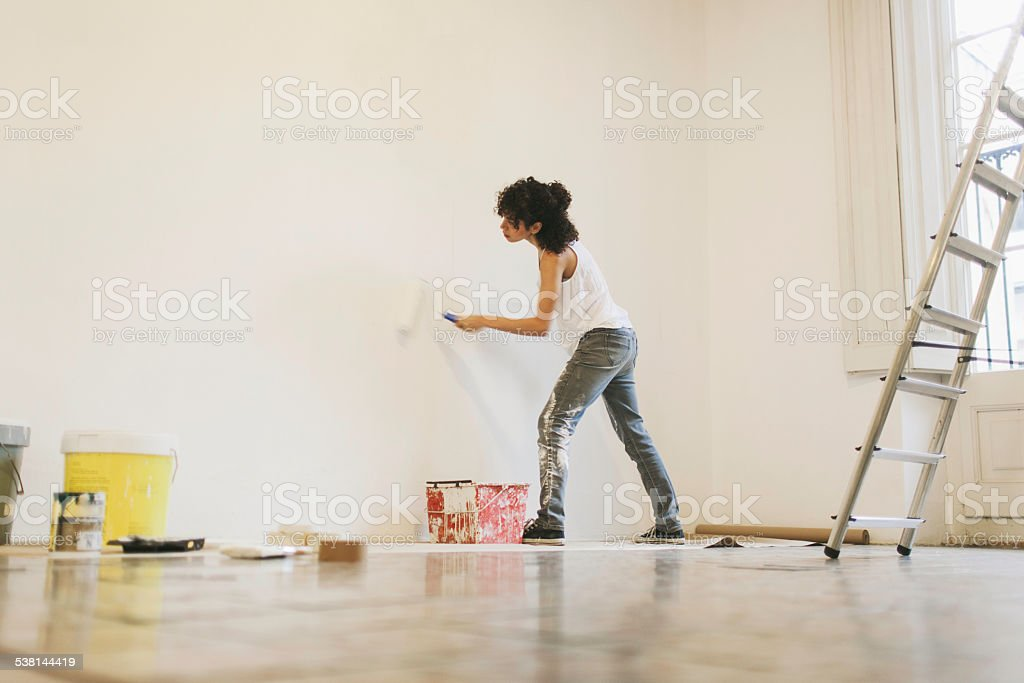 Young woman painting her new apartment. stock photo