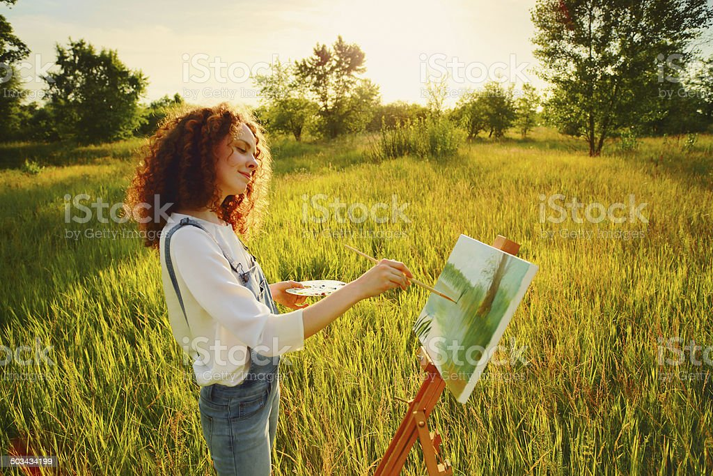 Young woman painting landscape in open air stock photo
