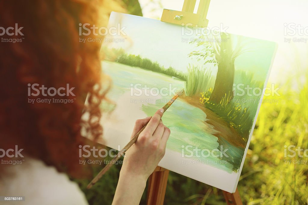 Young woman painting landscape in open air. stock photo