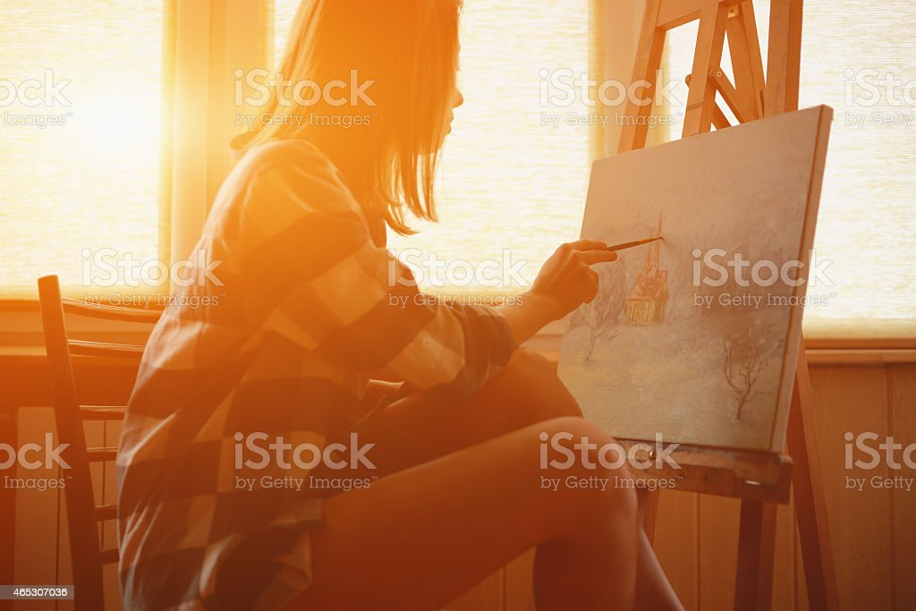 Young woman painting landscape near the window stock photo
