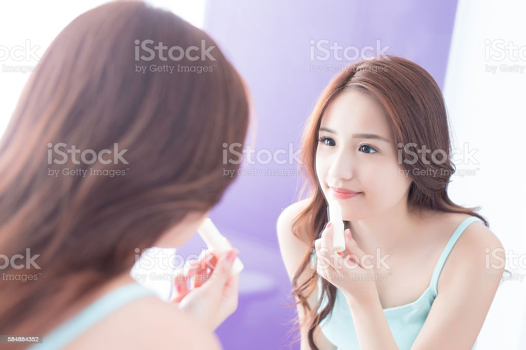 young woman painting  lip balm stock photo