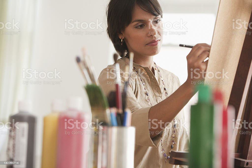 Young woman painting on easel stock photo
