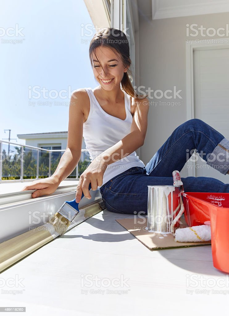 Young woman painting window trim stock photo