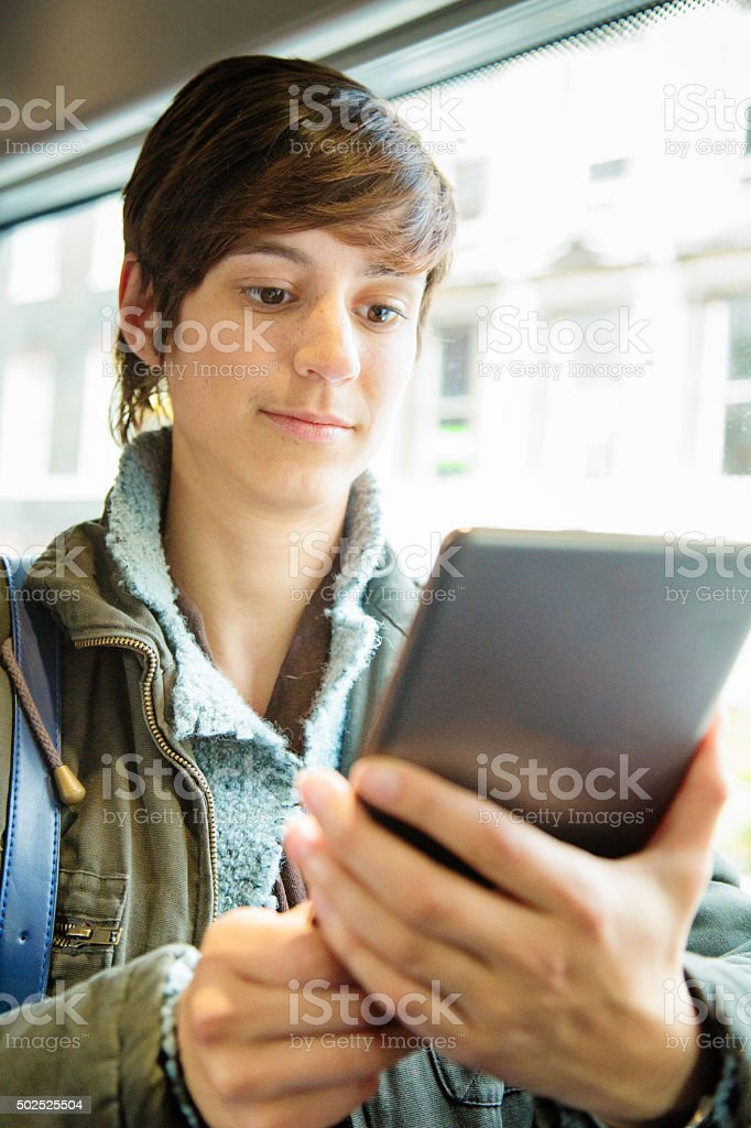 Young woman passing time with a tablet on bus ride stock photo