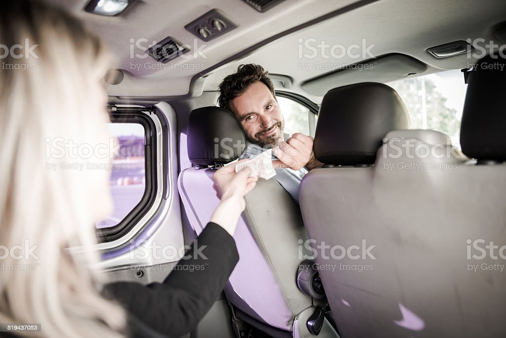 Young Woman Paying For The Taxi stock photo