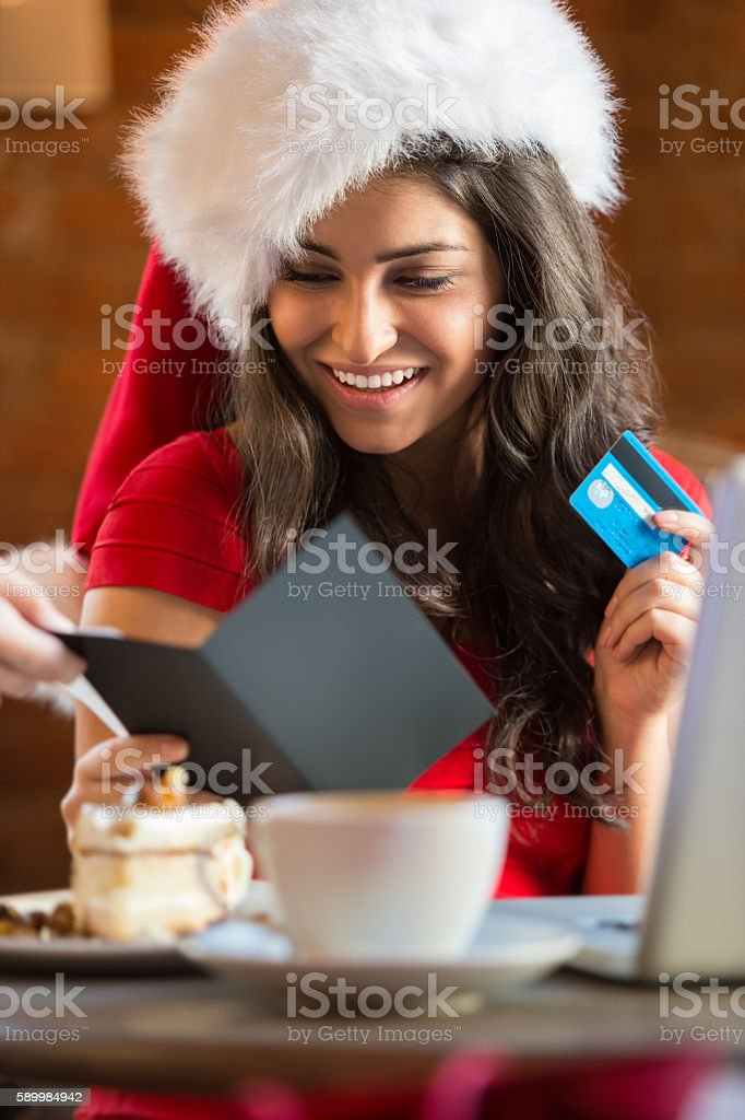 Young woman paying her bill in cafe wearing christmas hat stock photo