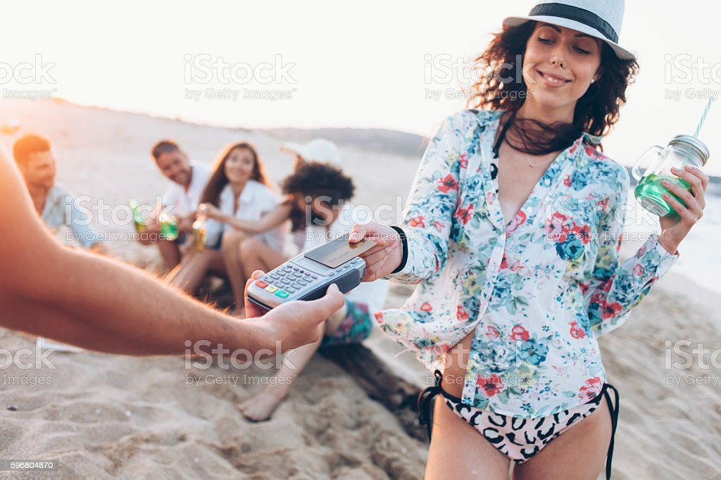 Young woman paying with credit card on beach stock photo