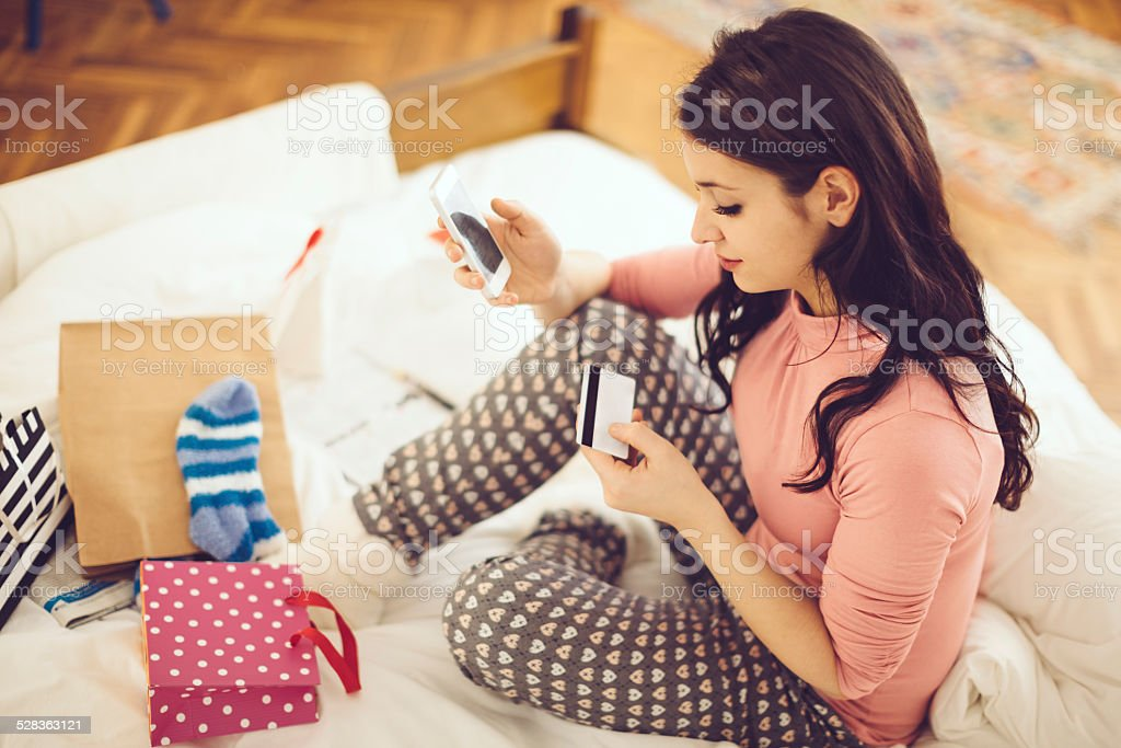 Young woman paying with her credit-card via cellphone stock photo