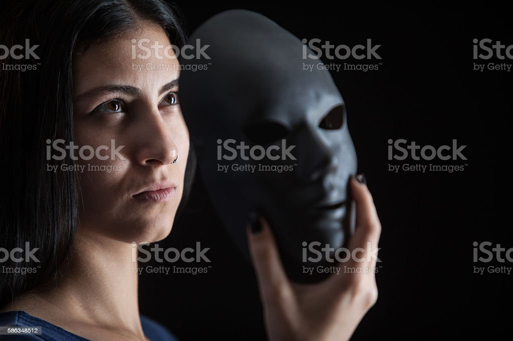 Young woman peeking behind mask in dark stock photo