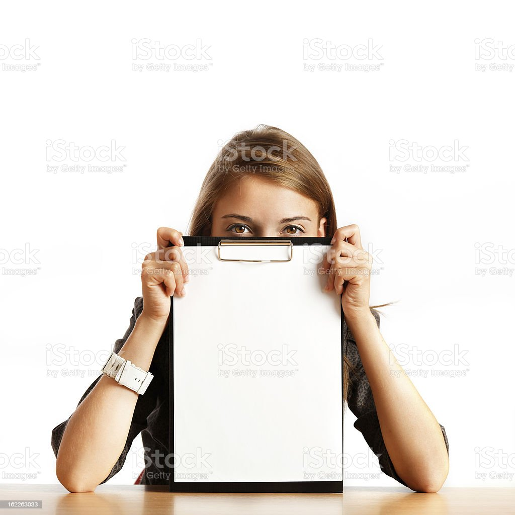 young woman peeking out behind a clipboard with blank paper royalty-free stock photo