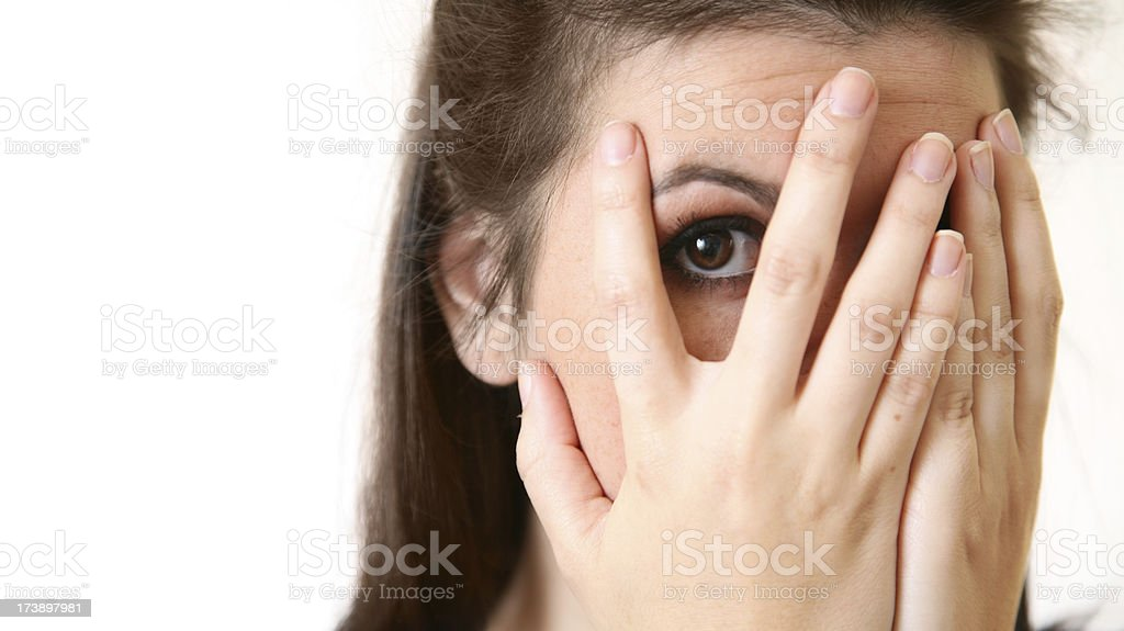 Young Woman Peeking Through Her Fingers, With Copy Space stock photo
