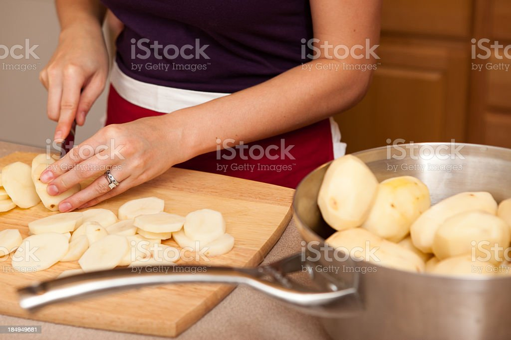 Young Woman Peeling Potatoes in Kitchen royalty-free stock photo