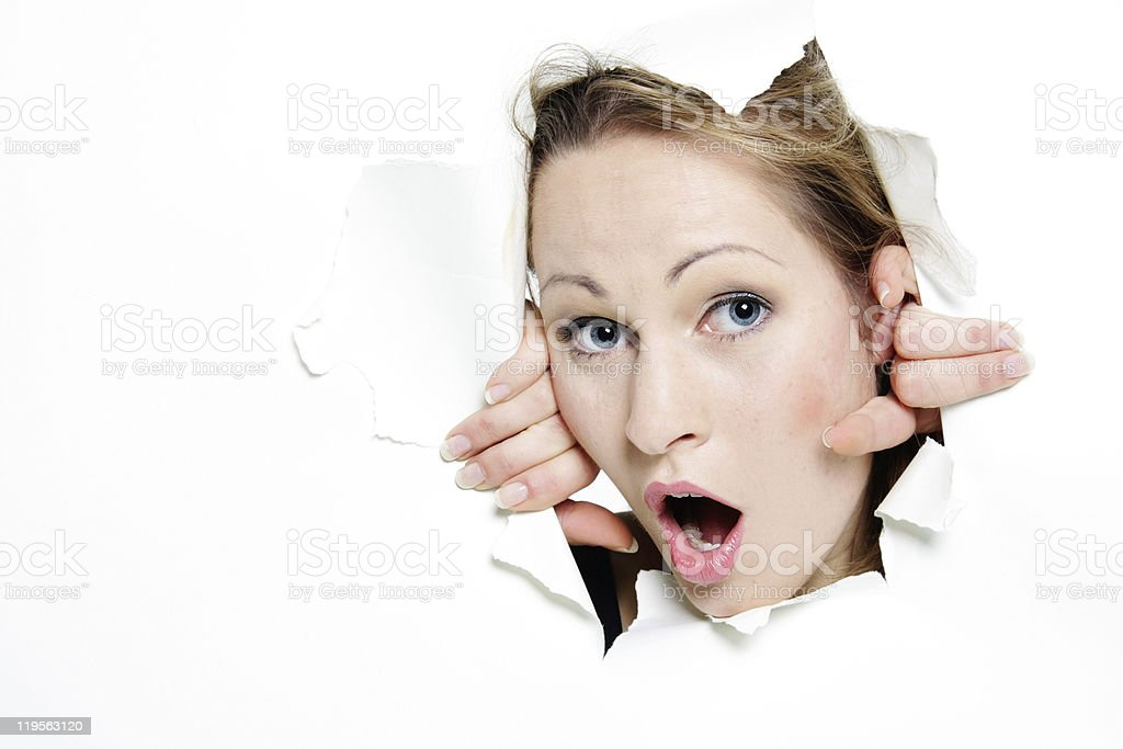 young woman peeping through hole in paper royalty-free stock photo