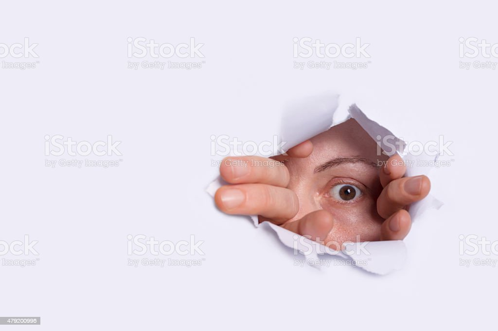 Young woman peeping through hole on paper. stock photo