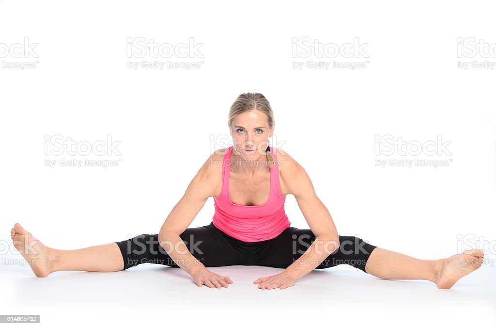Young woman performing a straddle split stretch stock photo