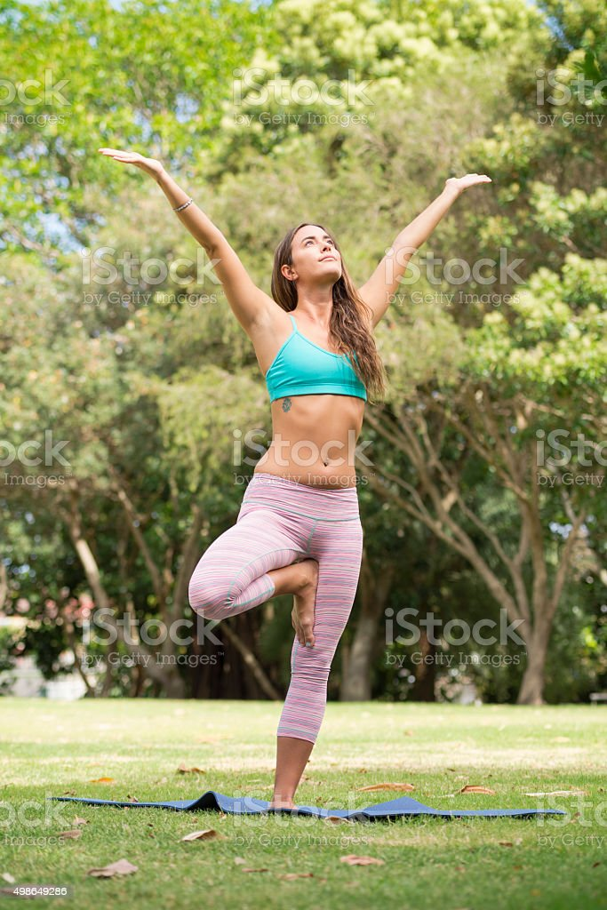 Young woman performing yoga at the park stock photo