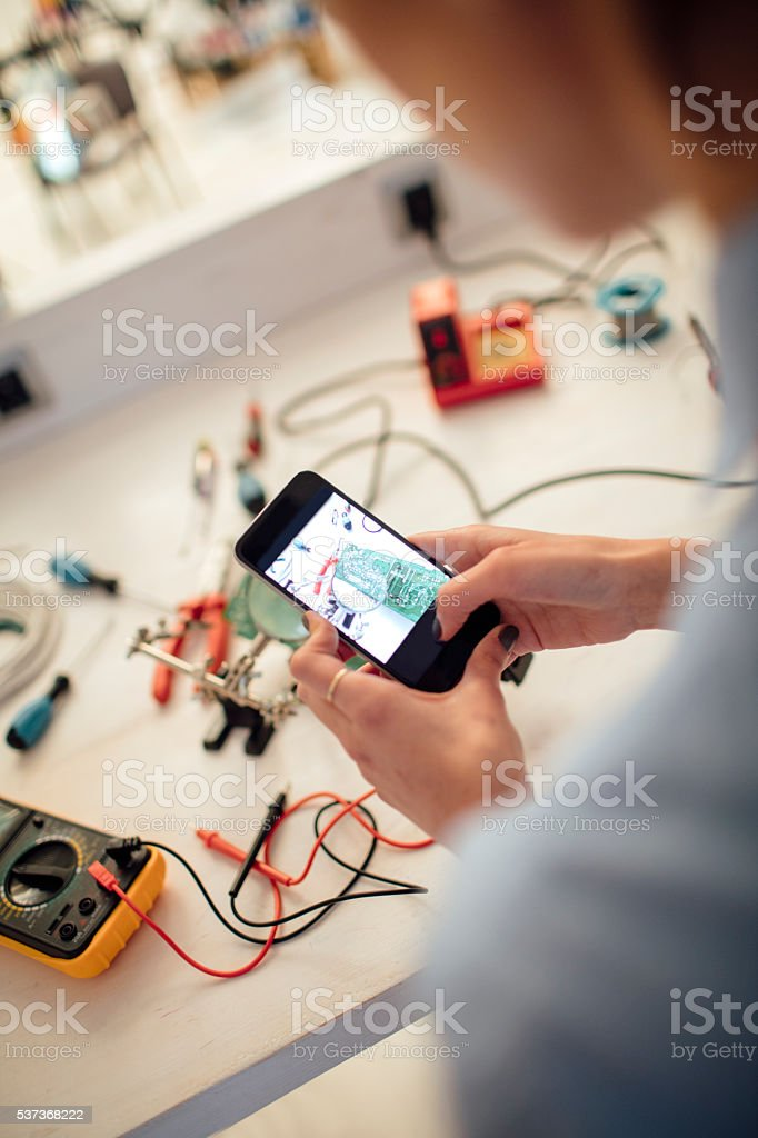 Young Woman Photographing Circuit Board In Her Office. stock photo