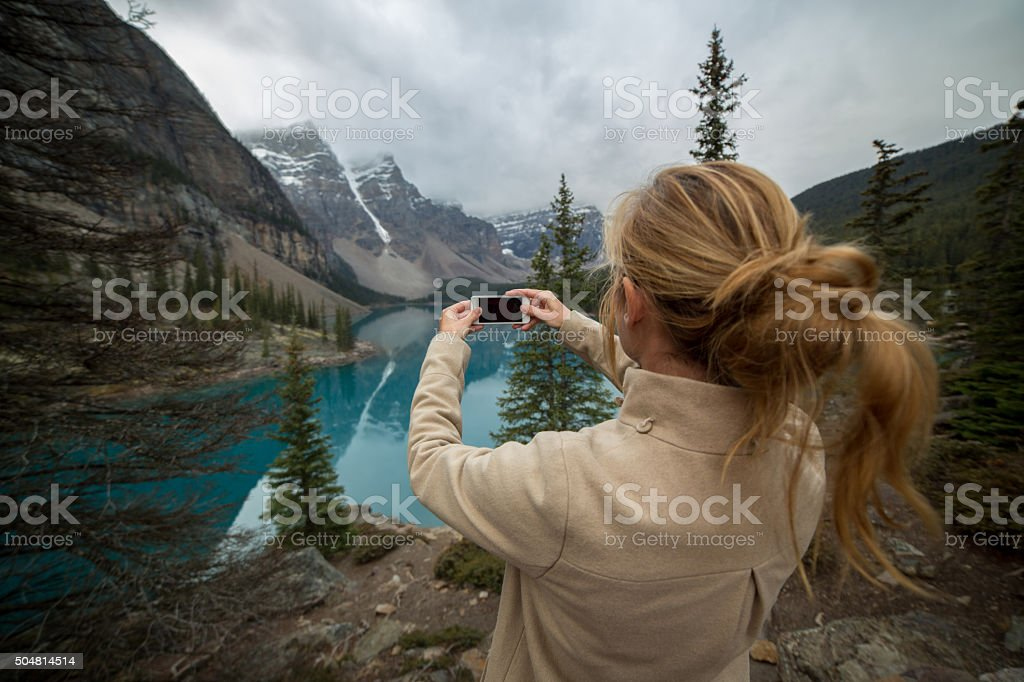 Young woman photographing Moraine lake using mobile phone stock photo