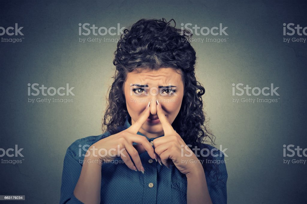 young woman pinches her nose with fingers looks with disgust something stinks stock photo