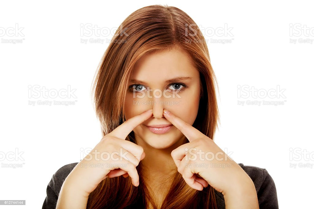 Young woman pinches nose with fingers hands looks stock photo