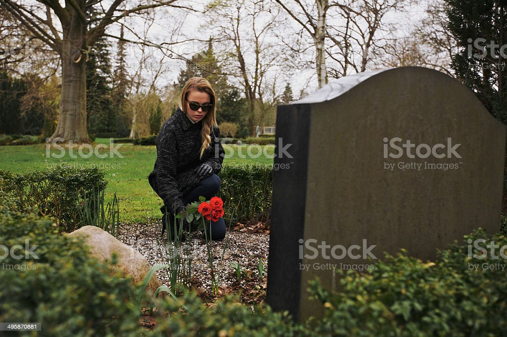 Young woman placing roses at a cemetery stock photo