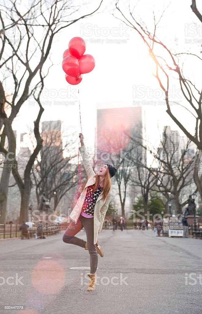 Young Woman playfully holding balloons stock photo