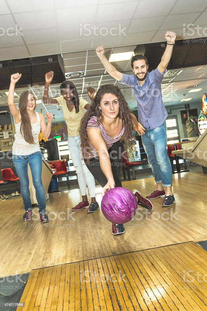 Young woman playing bowling with friends stock photo