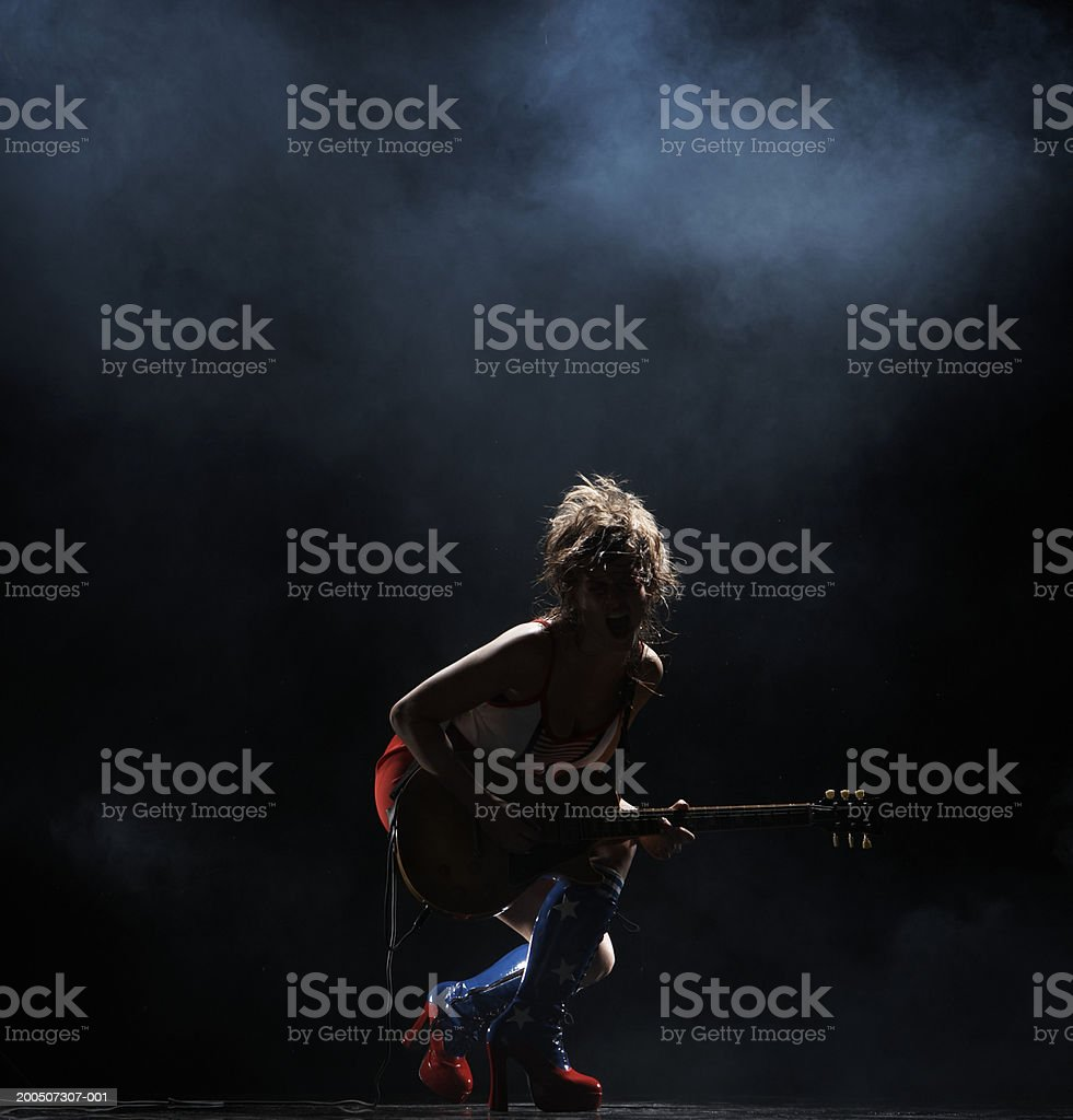 Young woman playing electric guitar on dark stage stock photo