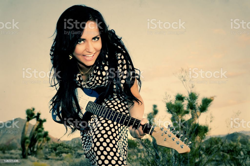 Young Woman Playing Guitar in Desert royalty-free stock photo